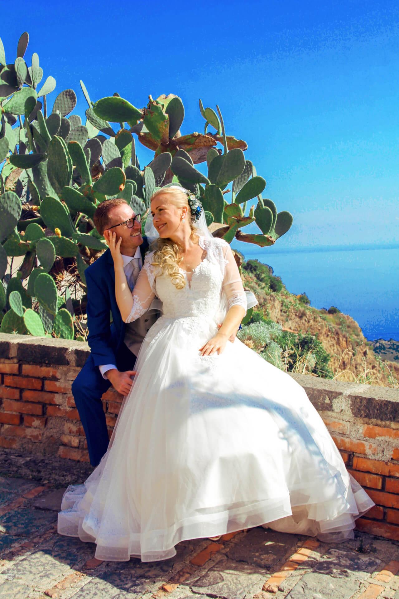 Fotografia novomanželov sediacich na múriku